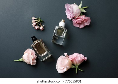 Bottles of perfume with flowers on dark background