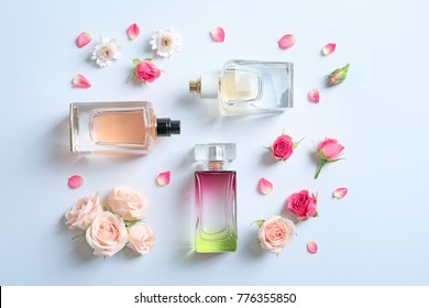Bottles of perfume with flowers on white background