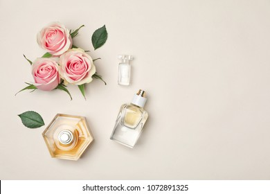 Bottles of perfume and roses on light background, top view
