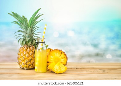 Bottles of pineapple juice with sliced pineapple fruit on wooden table with abstract  blue sea background , summer fruit drink concept
