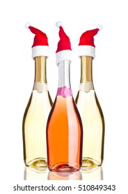 Bottles of pink yellow champagne with santa hat on white background
