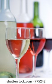 Bottles of red, white and rose wine behind clear filled glasses and a white isolated background