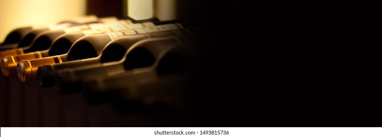 Bottles of red wine on a wooden shelf, panoramic banner with black background