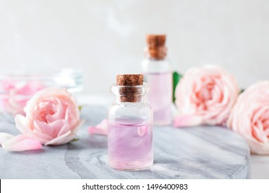 Bottles with rose essential oil and flowers on stone board