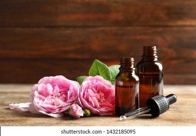 Bottles of rose essential oil, pipette and flowers on wooden table. Space for text