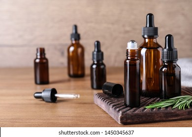 Bottles of rosemary essential oil on wooden table. Space for text