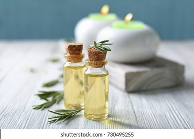 Bottles with rosemary oil and herb on wooden table
