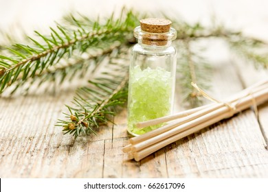 Bottles of sea salt and fir branches for aromatherapy and spa on wooden table background