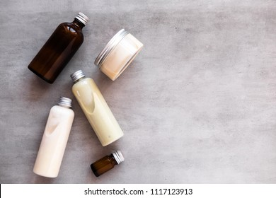 Bottles with spa cosmetic products from above on gray concrete table. Beauty blogger, salon treatments concept. Minimalism