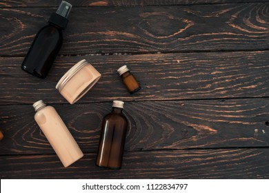 Bottles with spa cosmetic products from above on dark brown wood table. Beauty blogger, salon treatments concept. Minimalism, copyspace