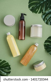 Bottles with spa cosmetic products on green background, top view. Beauty salon treatments concept.