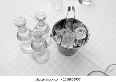 bottles with strong alcohol and ice bucket, closeup in white and black
