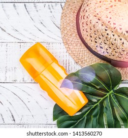 Bottles of sunscreen lotion and moisurizing spray agains sunburn. Summer skincare protection concept. Summer vacation background with straw hat and monstera leaf on white wooden background