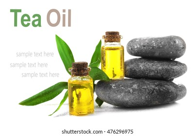 Bottles with tea tree essence and spa stones on white background. Space for text.