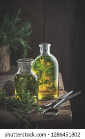 Bottles of thyme and rosemary essential oil or infusion and scissors on old wooden table.