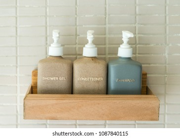 Bottles of toiletries in earth tone shade in a wooden holder