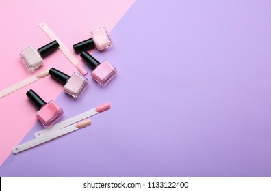 Bottles of varnish and artificial nails on color background