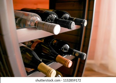 Bottles of white and red wine on a wooden shelf in private winery cabinet room interior