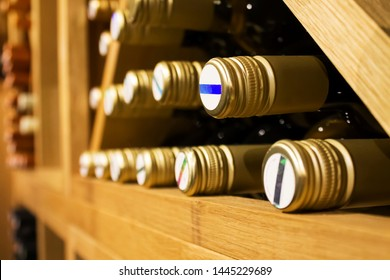 Bottles of white wine with golden colored wrap laying down on the wooden shelf in dark,fresh cellar