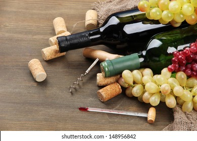 Bottles of wine, grapes and corks on wooden background