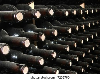 Bottles of wine in rows in wine cellar.