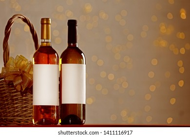 Bottles of wine and wicker basket with bow against blurred lights. Space for text