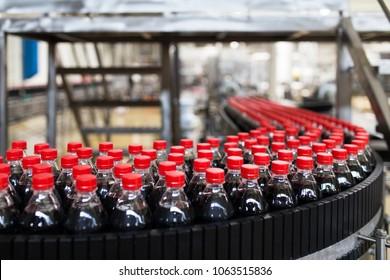 Bottling factory - Black juice or soft drink bottling line for processing and bottling juice into bottles. Selective focus.