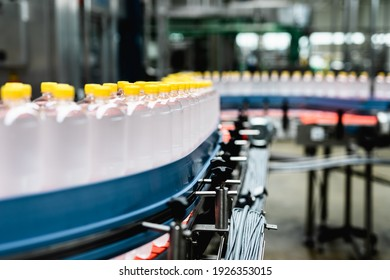 Bottling factory - Juice bottling line for processing and bottling lemon juice into bottles. Selective focus.