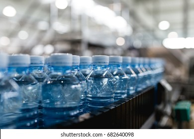 Bottling plant - Water bottling line for processing and bottling pure mineral carbonated water into bottles. Selective focus.