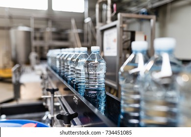 Bottling plant - Water bottling line for processing and bottling carbonated water into blue bottles. Selective focus.