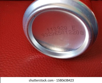 Bottom of canned placed on red floor, there is specific manufacturing day.