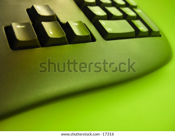 Bottom of a computer keyboard, focus on the arrow keys, with a bright green hue.