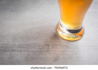 Bottom of glass of beer on a stone background.