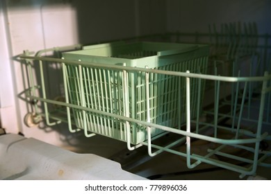Bottom rack of a dirty old dishwasher.