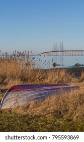 The bottom of a skiff on the beach of Oresund and the Oresund bridge in the background a winter morning in January