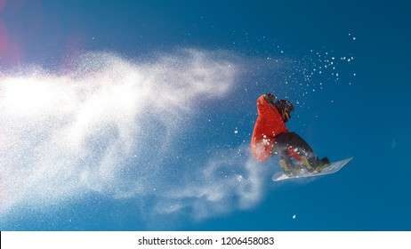 BOTTOM UP: Athletic young man jumps high in air and does a cool trick on his snowboard while riding in the sunny Alps. Spectacular action shot of pro snowboarder leaving a trail of snow in the air
