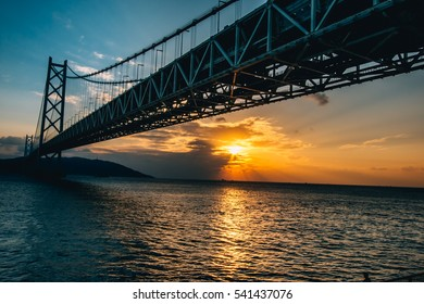 Bottom view of  Akashi Kaikyo Bridge and Sunset. the great architecture of suspension bridge, spanning the Seto Inland Sea from Awaji Island to Kobe, Japan