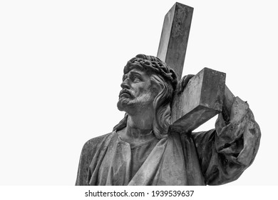 Bottom view of an ancient statue of Jesus Christ with cross. Selective focus on eyes.