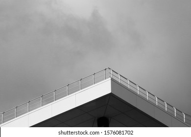 Bottom view of angular terrace roof with steel balustrade. Close-up photo of modern building fragment under cloudy sky. Minimalist business architecture image with background for text.