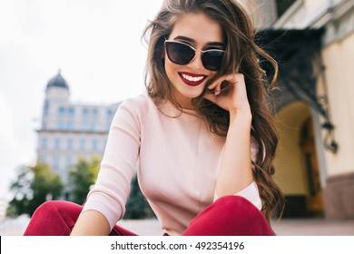 Bottom view of attractive student girl in sunglasses with snow-white smile, long hairstyle and vinous lips chilling in city.