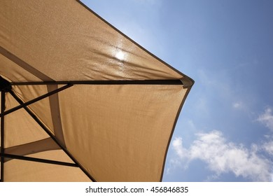 Bottom View Of Beach Umbrella Or Parasol And Sun Light Through It, Blue Sky With  Cirrus Clouds In The Background