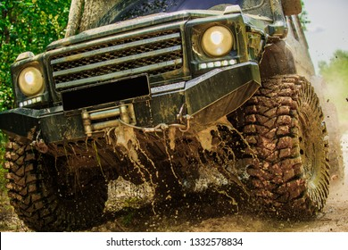 Bottom view to big offroad car wheel on country road and mountains backdrop. Motion the wheels tires and off-road that goes in the dust on the sand