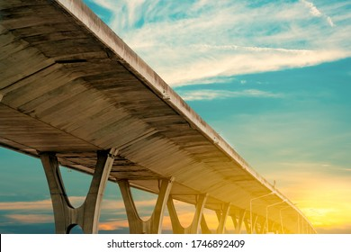 Bottom view of elevated concrete highway. Overpass concrete road. Road flyover structure. Modern motorway with golden sunrise sky. Concrete bridge engineering construction. Bridge architecture.