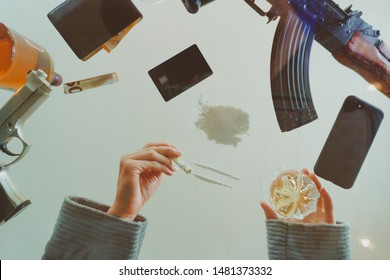 Bottom view (flat lay) through a glass table of woman's hands with a rolled euro bill (banknote) for sniffing cocaine (white powder), guns (AK47), bottle and glass of whiskey and a credit card on it