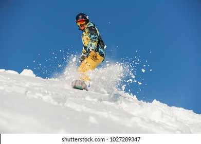 Bottom view of freeride snowboarder sliding down the snowy slope against the clear blue sky