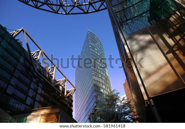 Bottom view of glass skyscraper and modern architectural structures.