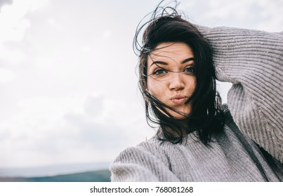 Bottom view of happy and funny brunette woman taking self portrait and blowing kiss on sunlight background. Cute female take selfie from her device. People, travel and lifestyle concept. Cover mood.