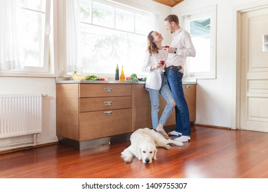 Bottom view happy newlyweds a beautiful woman and a young guy are sitting in the kitchen and drinking their morning coffee while enjoying a sunny morning next to the dog