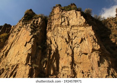 Bottom view of a huge rocky mountain slope, a huge uneven yellow rock, red lichens and bushes on the rock, summer, sunny, sky with clouds