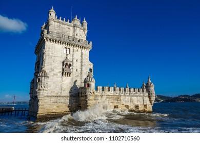 Bottom view of Lisbon Torre de Belem against blue sky with breaking waves